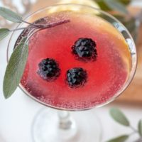 an overhead shot of a blackberry martini with a sage leaf resting on top