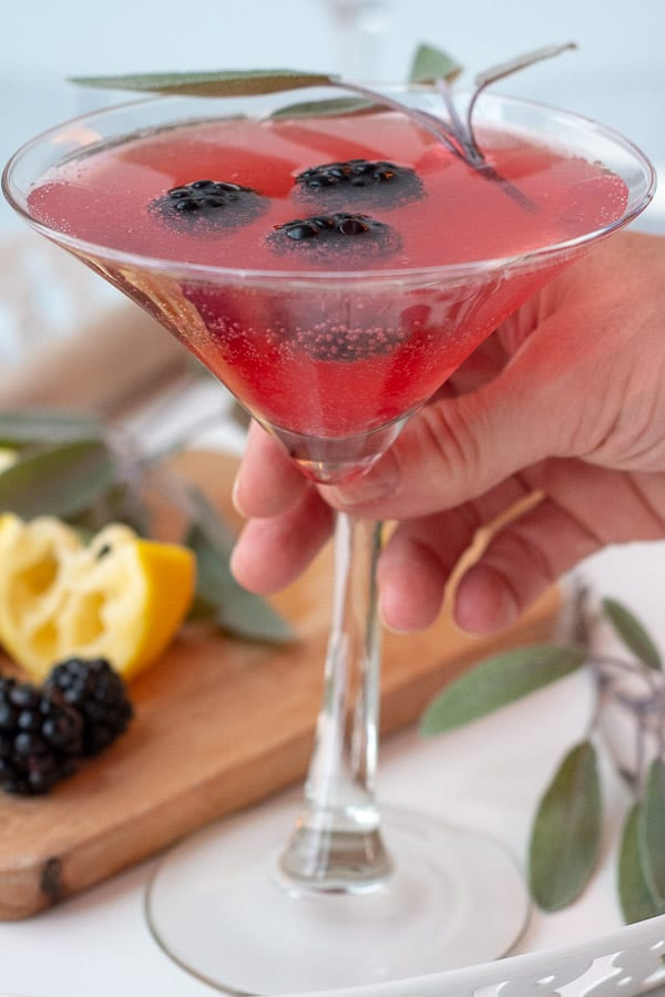 a hand about to lift up a martini glass filled with a blackberry martini