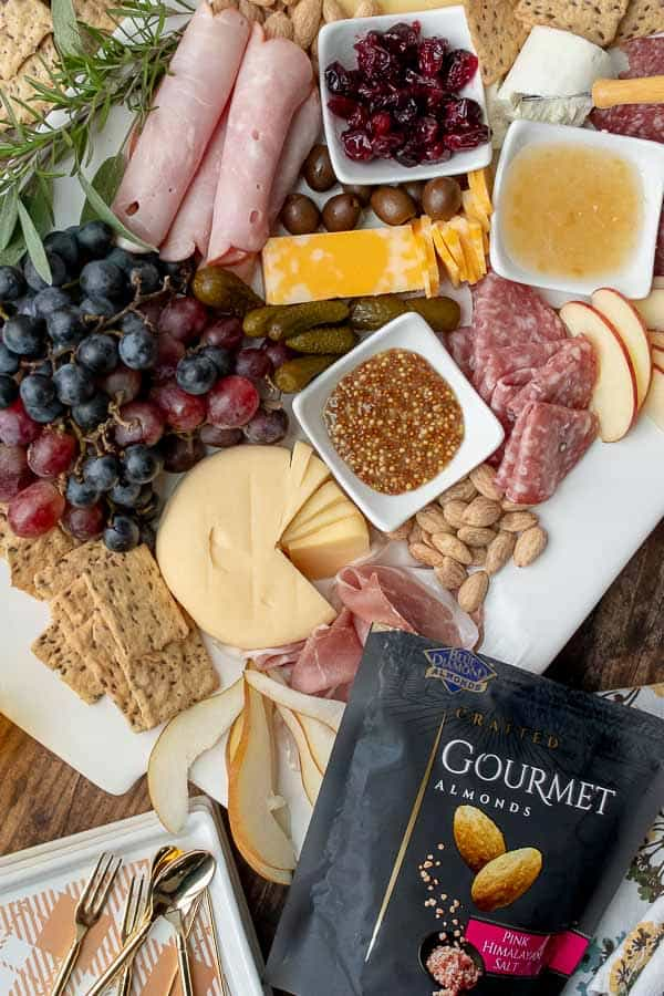 an overhead shot of a charcuterie board with plates nearby