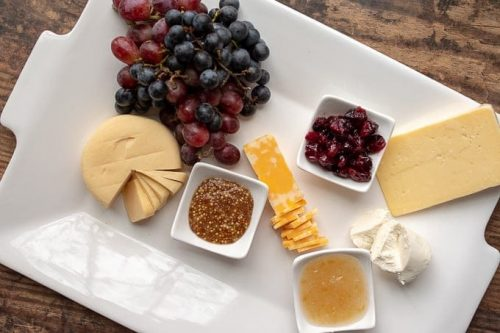 second step of how to make a charcuterie board - adding cheeses