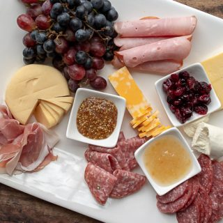third step of how to make a charcuterie board - adding meats