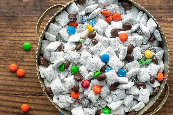 an overhead shot of nutella puppy chow in silver bowl with m&ms laying nearby