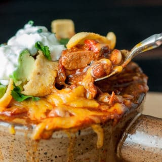 a close up of a spoon taking out a bite of chicken chorizo chili with cheese