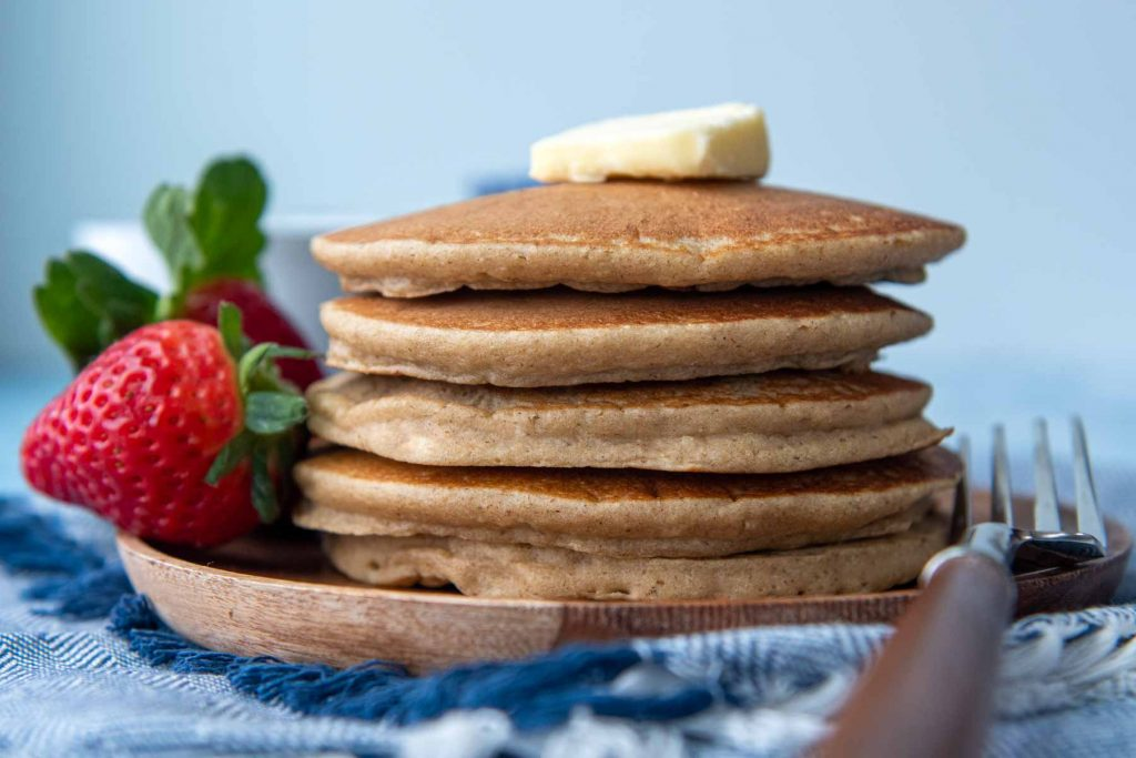 a stack of flourless pancakes on a wood plate with a piece of butter on top
