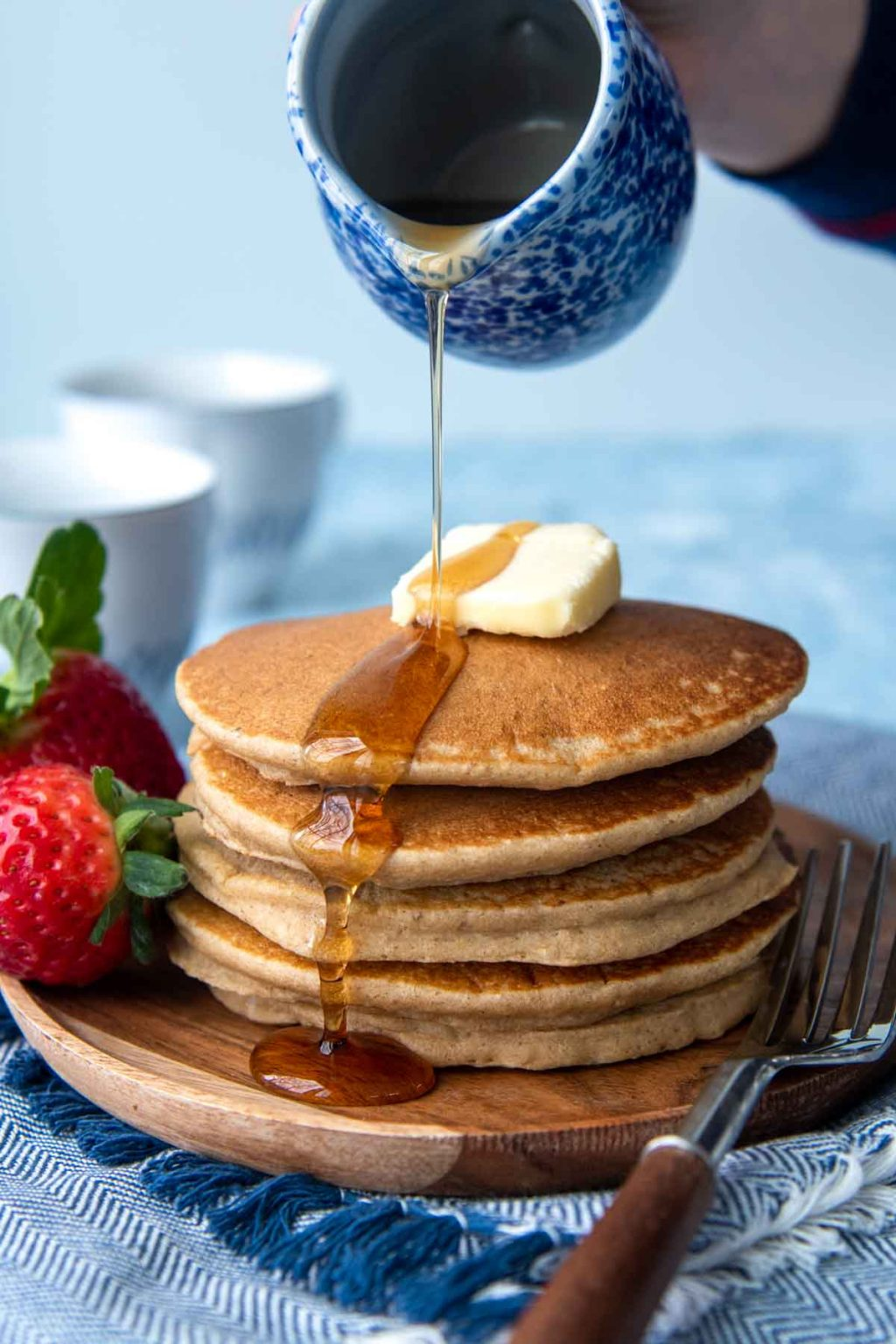 syrup being poured on uncut flourless pancakes stack