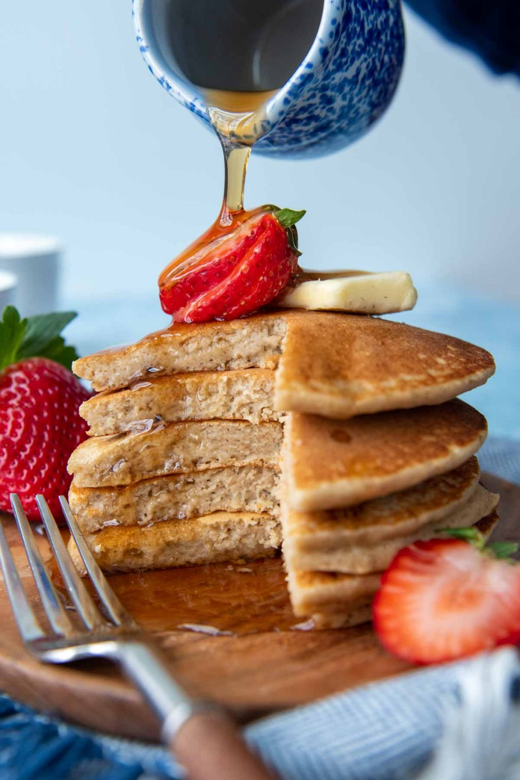 a stack of cut pancakes with a strawberry on top and syrup dripping down