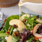 maple vinaigrette being poured from a white dressing container onto the apple pecan salad
