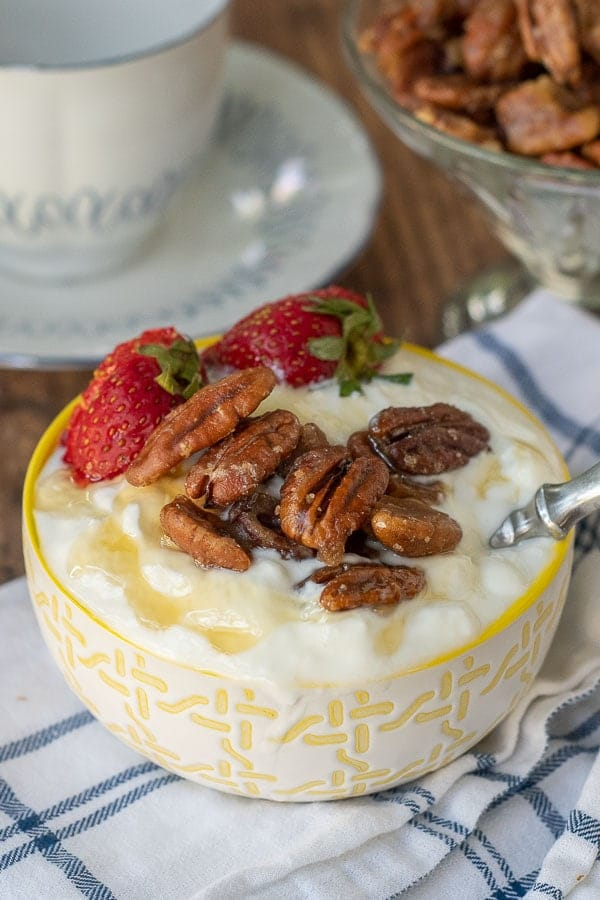 candied pecans in a bowl of yogurt with honey