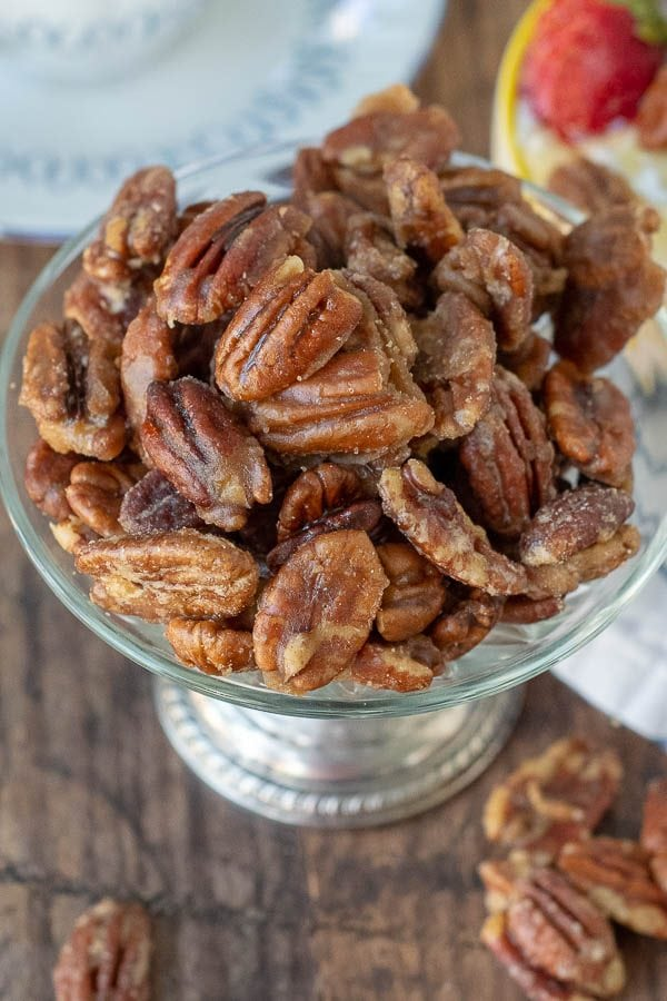an overhead shot of candied pecans in an antique silver bowl