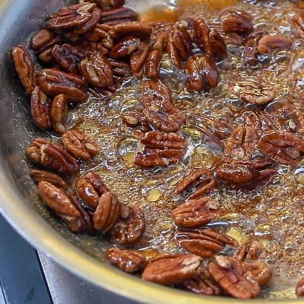 second step of how to make candied pecans - stir in pecans