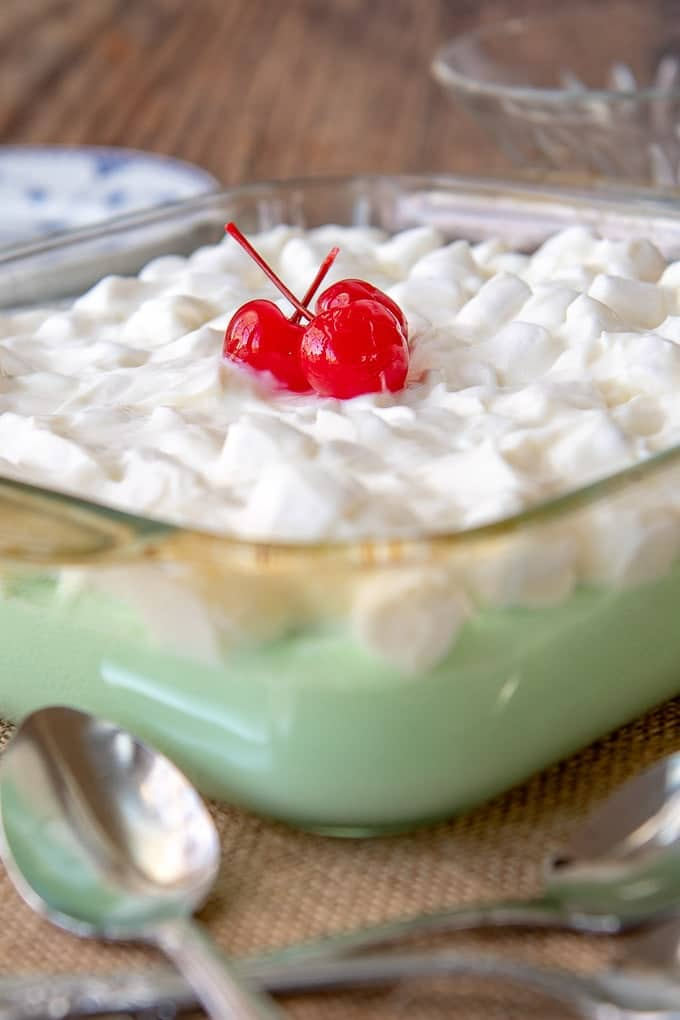 a shot of lime jello salad in a square glass dish with sour cream marshmallow topping