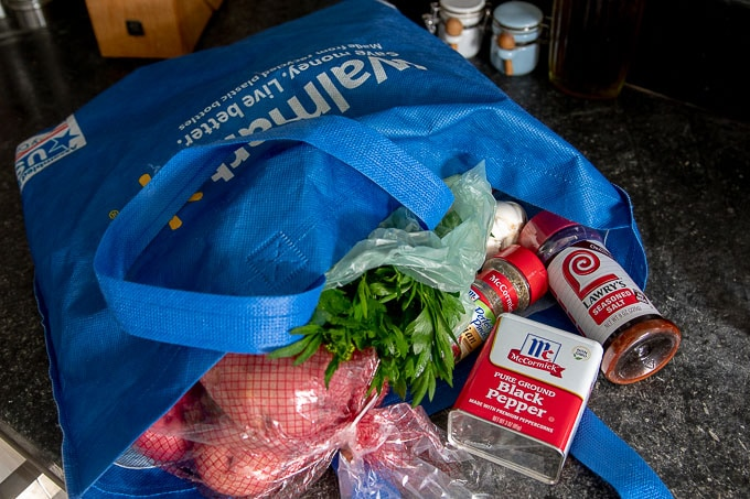 a shopping bag on a counter with the ingredients to make grilled potatoes