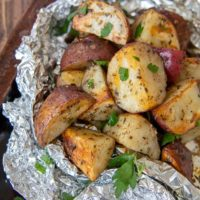 a close up of grilled red potatoes in an opened foil packet