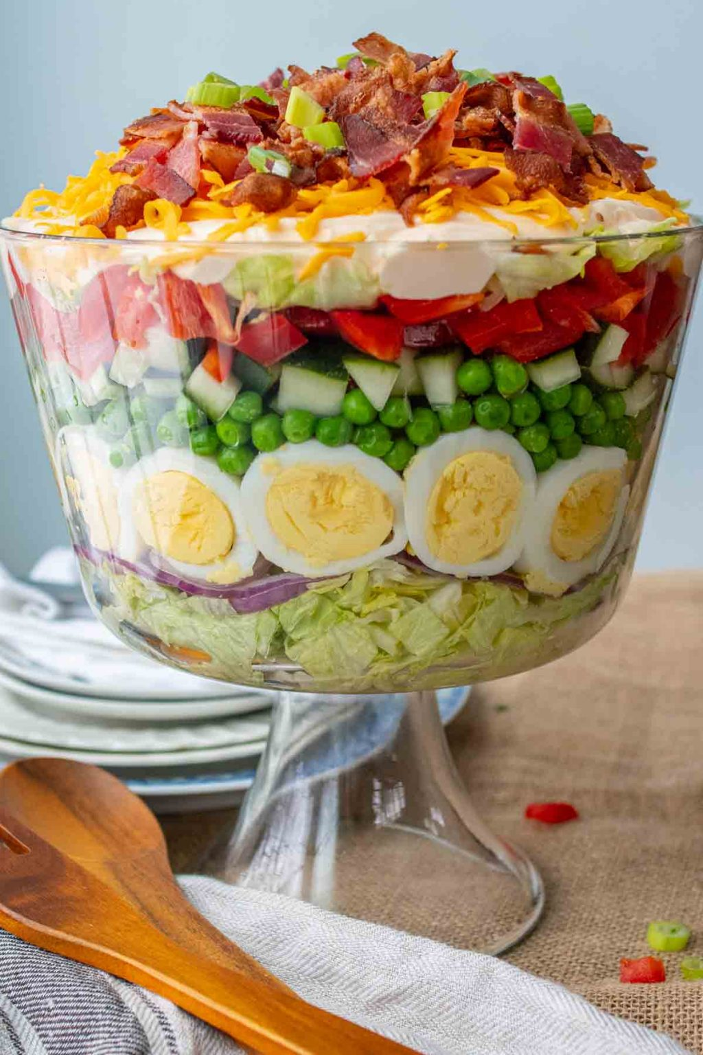 trifle bowl of 7 layer salad with wood serving utensils laying next to it
