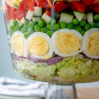 close up of 7 layer salad layers in a glass trifle bowl