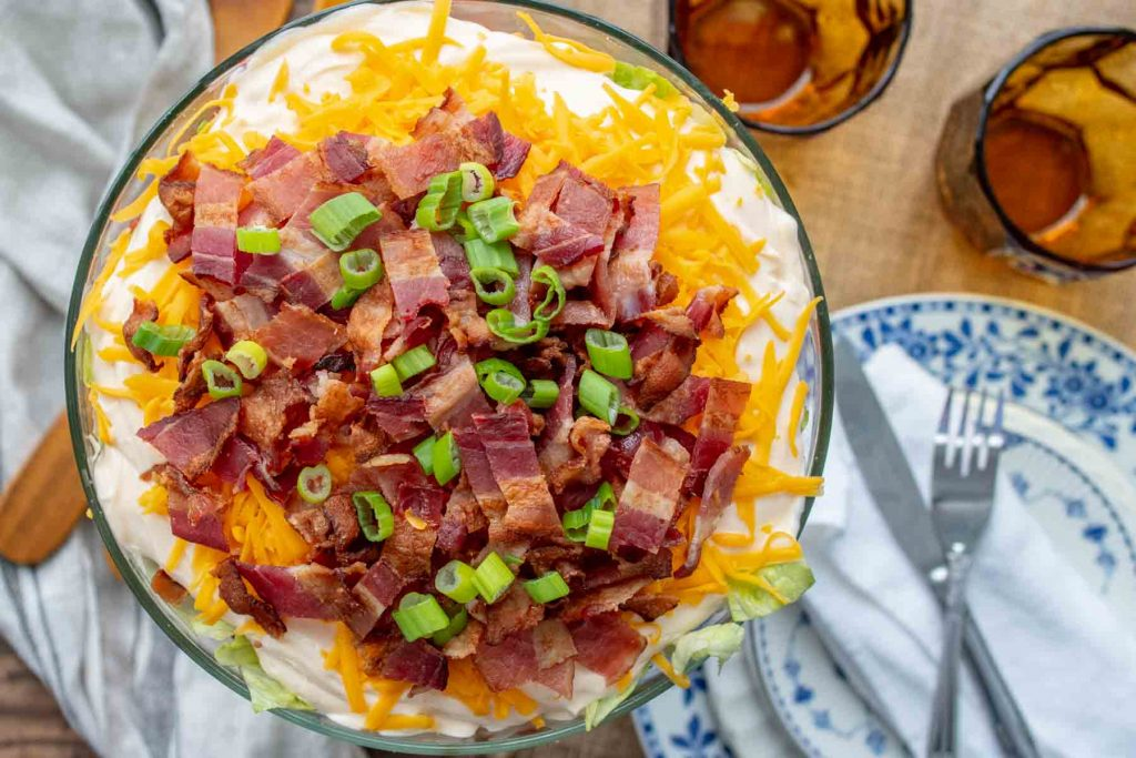 overhead shot of salad with bacon and cheese on top