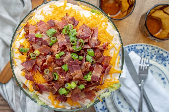 an overhead shot of seven layer salad with bacon, cheese, and dressing on top