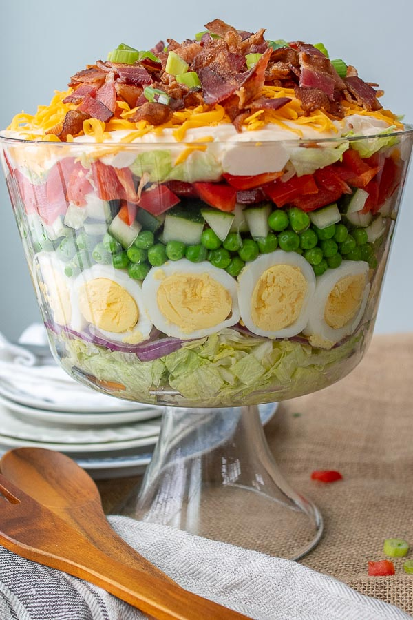 a seven layer salad in a glass trifle bowl with wooden spoon laying next to it