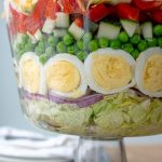 a close up of the peas and hard boiled eggs layer in 7 layer salad