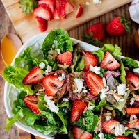 overhead shot of strawberry green salad with feta cheese on top