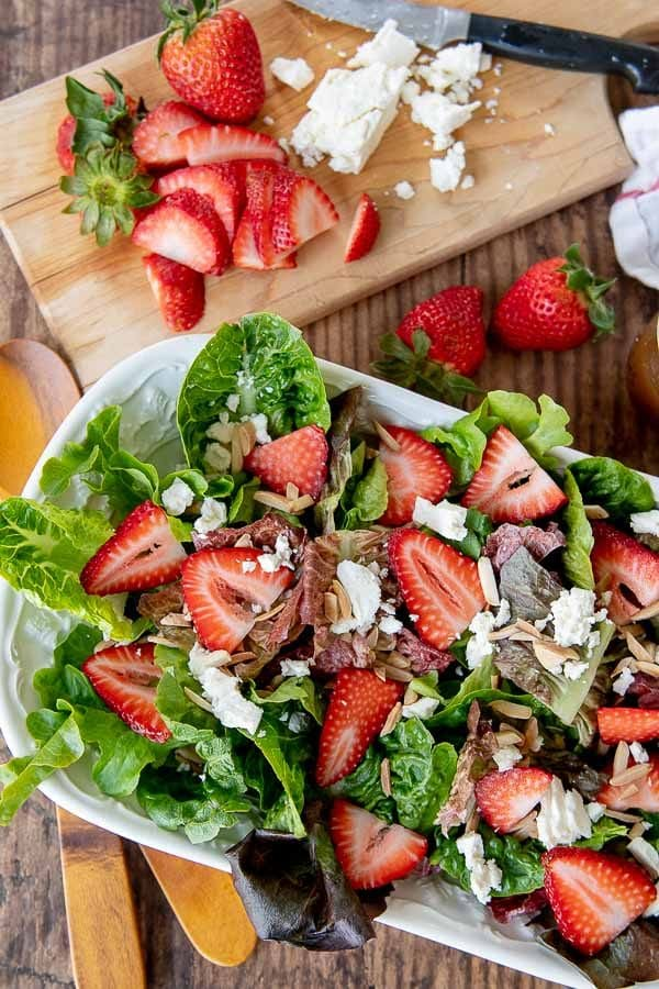 an overhead shot of strawberry salad in a white bowl with cutting board next to it