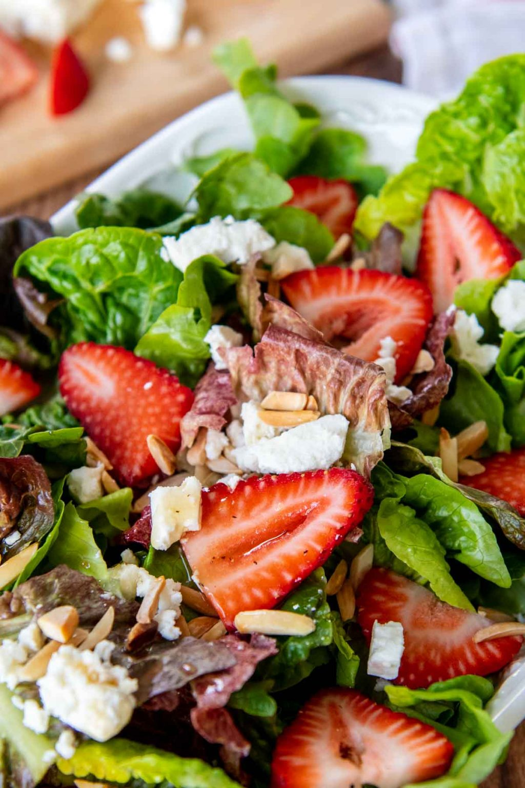 close up of strawberries and lettuce with dressing drizzled over top