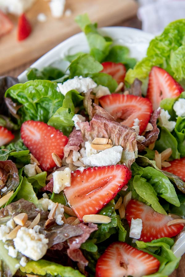 a close up so strawberry salad in a white bowl with cutting board behind