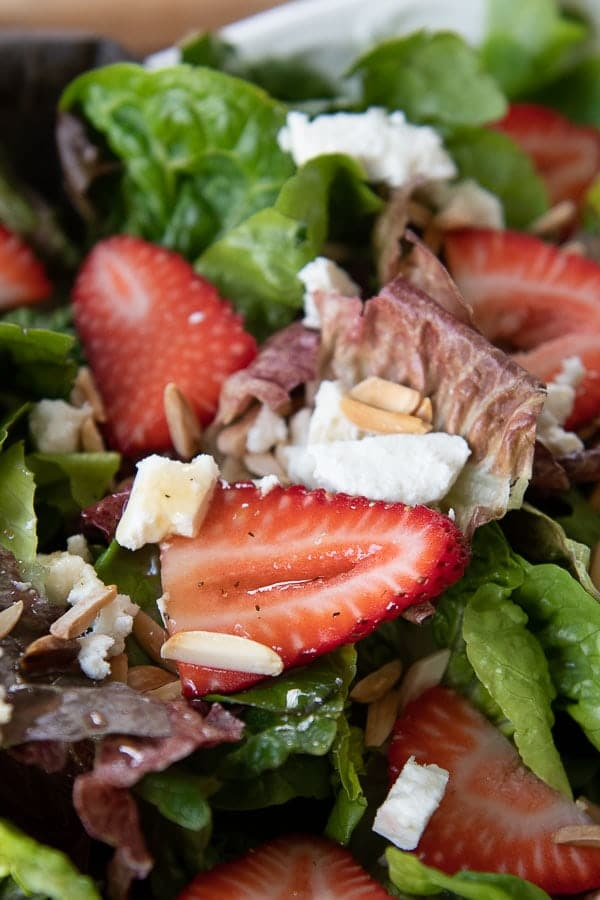 a close up of sliced strawberry on salad with dressing poured over