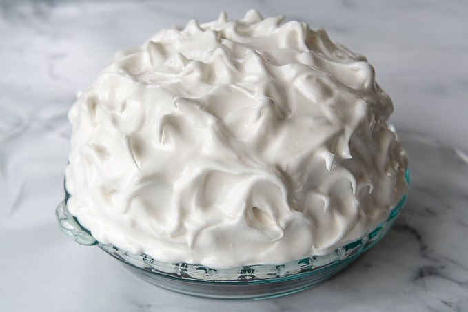 shows how the meringue covers the entire cake in baked alaska before baking
