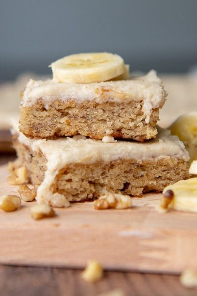 a stack of two banana bars with a sliced banana piece on top