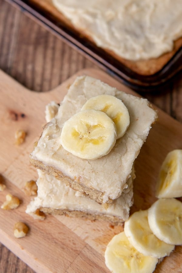 an overhead shot of banana bars stacked on top of each other with sliced bananas on top