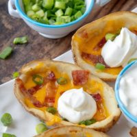a close up of a loaded potato skin with a dollop of sour cream on top
