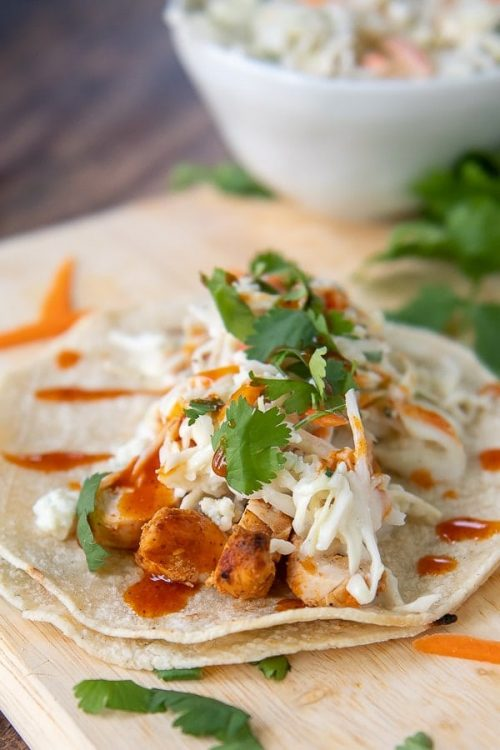 a close up of buffalo chicken tacos on a wooden cutting board