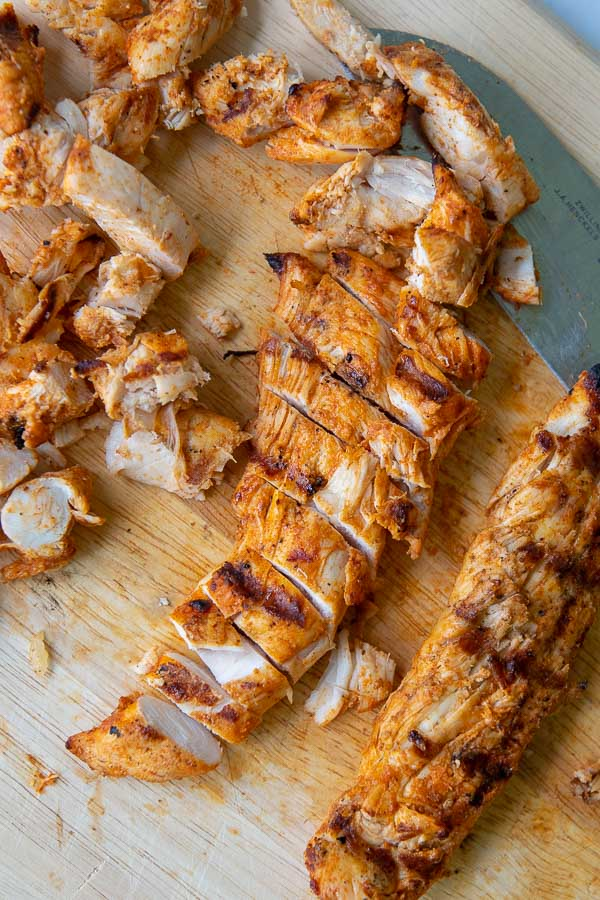 grilled buffalo chicken on a wooden cutting board sliced up