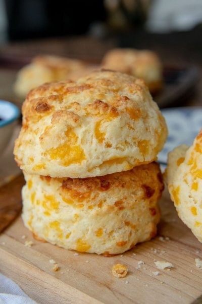 a stack of 2 gluten free cheese scones on a wood cutting board
