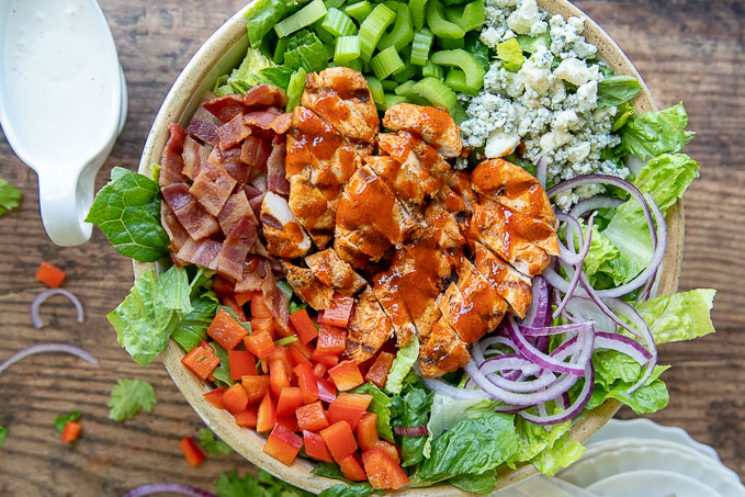 an overhead shot of a large salad bowl containing an assembled buffalo chicken salad