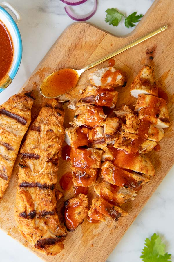 chopped grilled buffalo chicken on a wooden cutting board