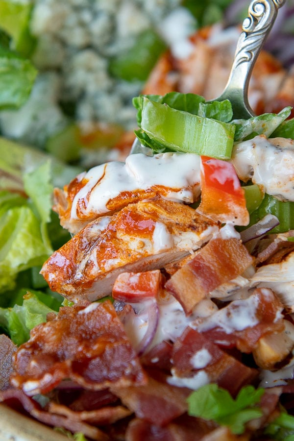 a close up of chicken tossed with ranch and buffalo sauce on the salad