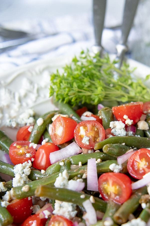 close up shot of halved tomatoes in green bean salad serving bowl