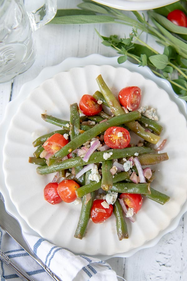 a white scalloped plate with a serving of cold bean salad