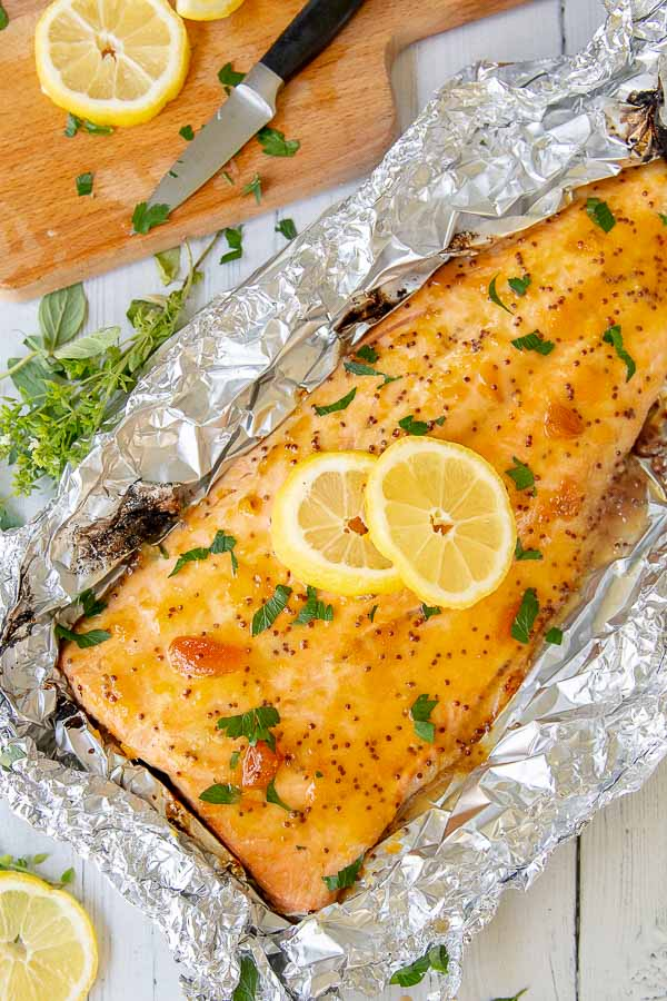 overhead shot of a large salmon fillet with parsley and lemon on top