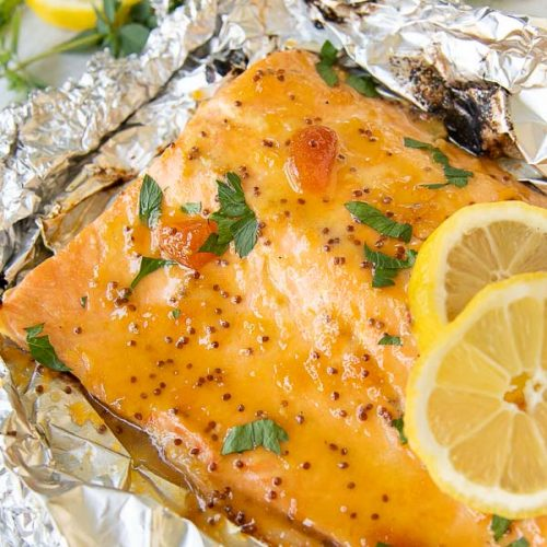 grilled salmon nested in foil with lemon slices laying on top