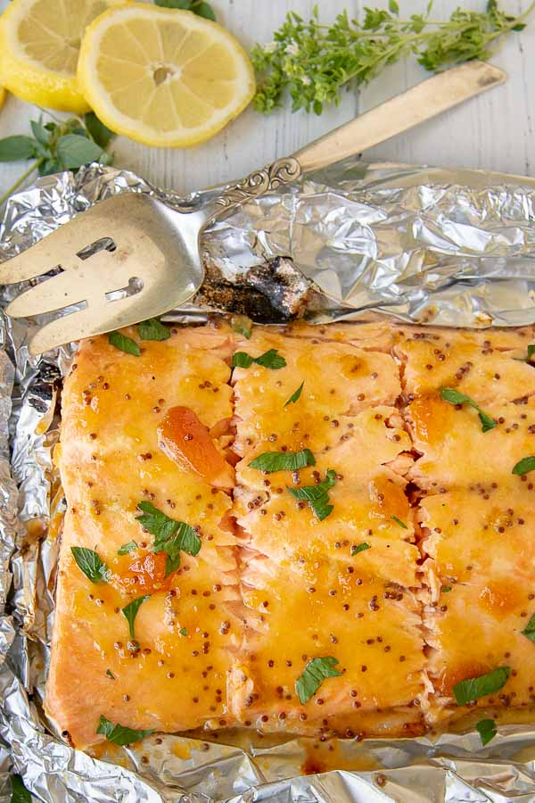 a large salmon fillet cut into pieces with a large serving spoon resting by