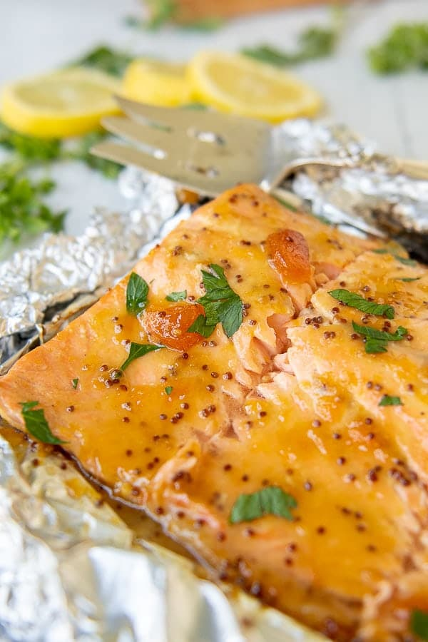 a close up of grilled salmon laying on crumbled foil with apricot mustard glaze