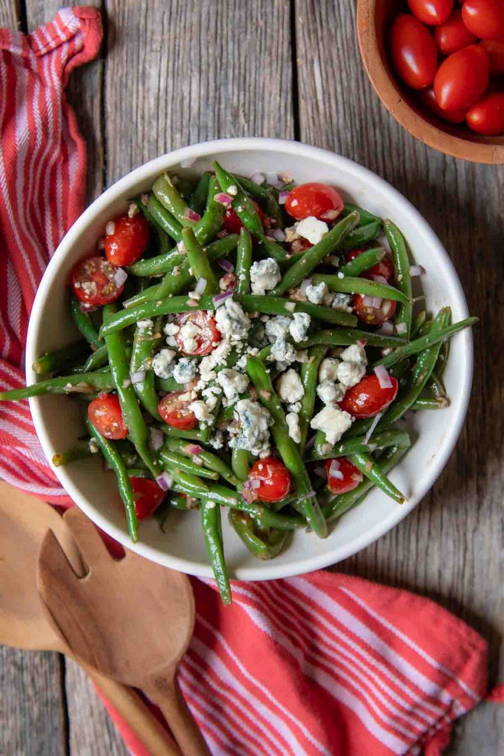 overhead of green bean salad in a white bowl with a red towel and serving tongs