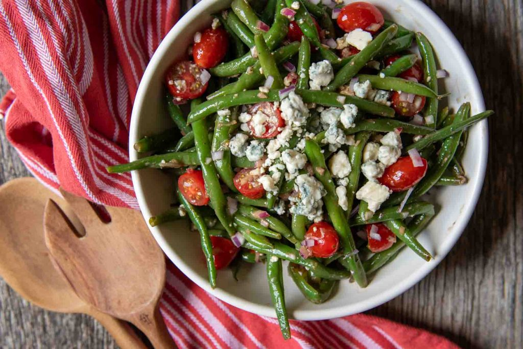 close up landscape of green bean salad with red towel