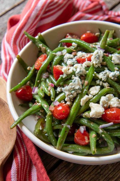 a close up of a serving bowl of beans, blue cheese and tomatoes