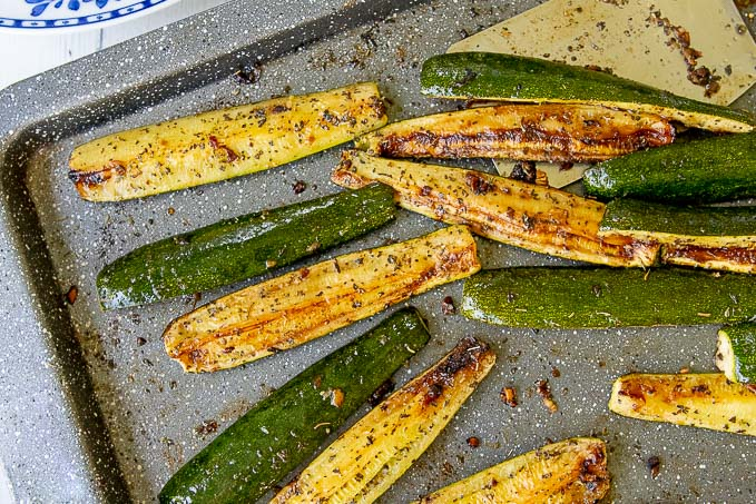 a close up of baked zucchini on a sheet with a spatula
