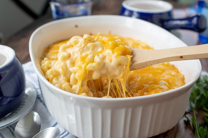 a wooden spoon holding up a serving of baked mac and cheese from a white casserole dish