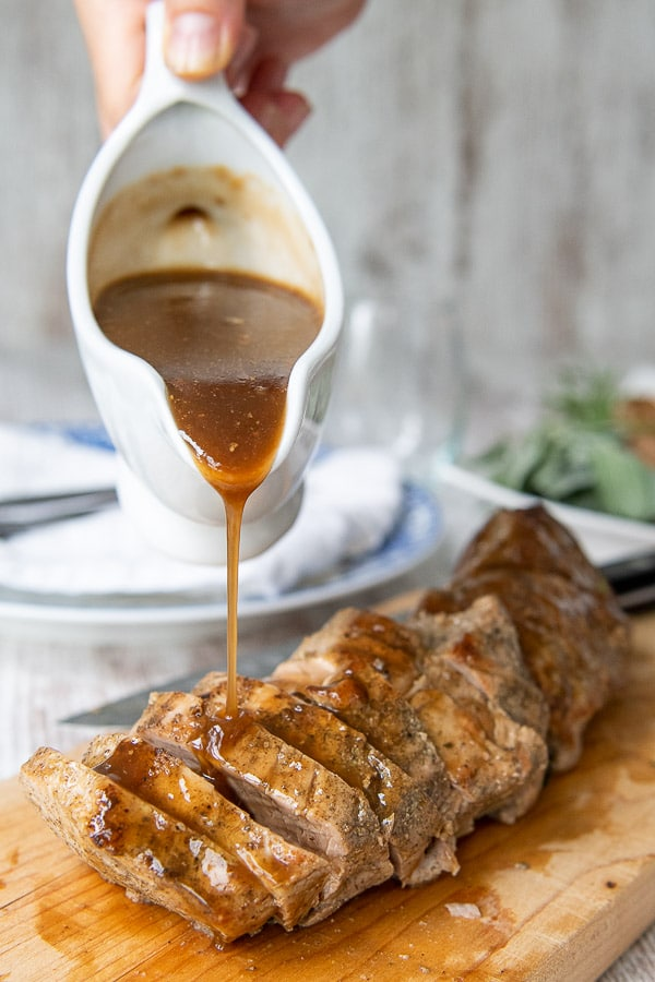 a gravy boat pouring on balsamic sauce on top of cut pieces of instant pot pork